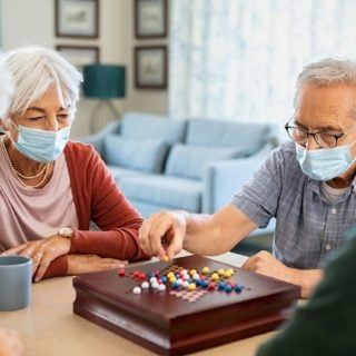 Four people with white hair sit around a small table playing a board game, all wearing face masks